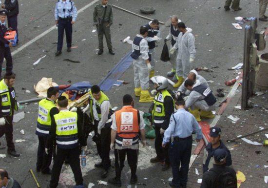 Des enquêteurs entourent le corps du kamikaze à la suite de l'attentat près de la pizzeria Sbarro, à la jonction de Jaffa Road et de King George Street à Jérusalem.
