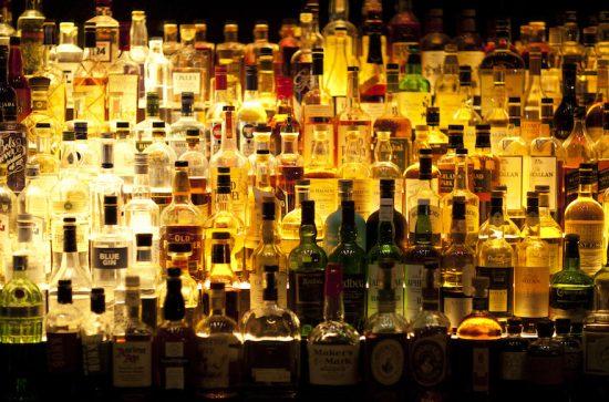 Various liquor bottles sitting behind bar, backlit