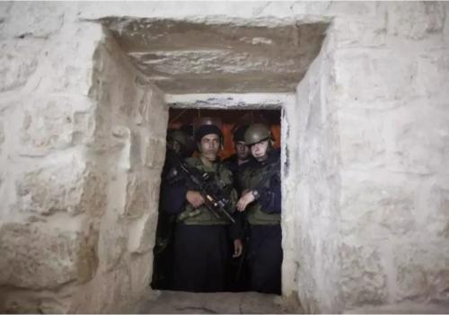Des soldats israéliens montent la garde devant une meurtrière au tombeau de Joseph alors que des fidèles juifs prient à l'intérieur, dans la ville de Naplouse, en Cisjordanie, au début du 4 juillet 2011. (Crédit photo: REUTERS / NIR ELIAS)