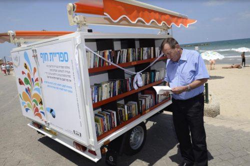 Le maire de Tel Aviv-Jaffa, Ron Huldai, consulte la bibliothèque de prêt sur la plage.
