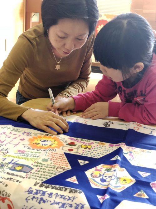 Des résidents de Tokyo écrivant leurs souhaits sur un drapeau israélien.