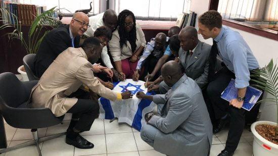 Des fonctionnaires à Abidjan, en Côte d'Ivoire, signent un drapeau israélien.