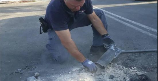 Un policier manipulant une roquette qui a atterri au Conseil régional d'Eshkol (Photo: Police israélienne)