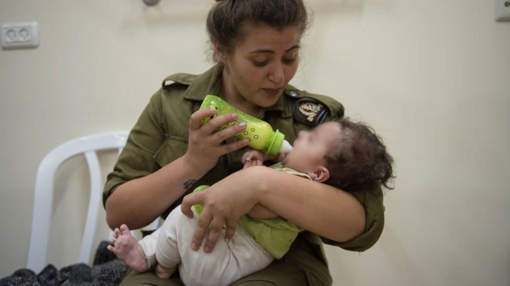 Une soldate israélienne donne le biberons à une bébé syrien