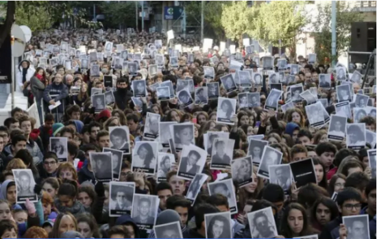 Les gens brandissent des photos des victimes de l'attentat à la bombe contre le centre juif AMIA. (REUTERS / Enrique Marcaria