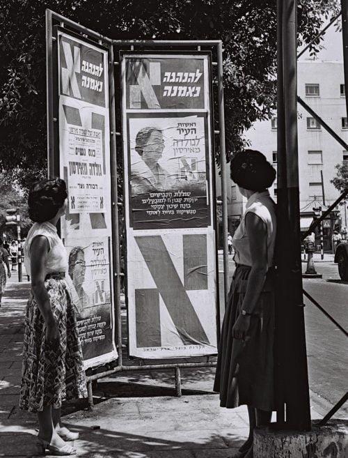 Deux femmes regardent les affiches de la campagne de Tel Aviv avec Golda Meyerson (Meir), qui a perdu par deux voix. Photo de Moshe Pridan / GPO