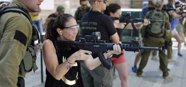 Foreign tourists are taught how to use a gun as they participate in a two hour anti-terror course at the Caliber 3 shooting range, near the Israeli occupied West Bank settlement of Efrat on July 18, 2017. The Caliber 3 shooting school has become an attraction for tourists, who are taught how to handle weapons, who participate in paintball or who learn Krav Maga, the self-defence method using boxing and martial arts developed by the Israeli military. / AFP PHOTO / MENAHEM KAHANA