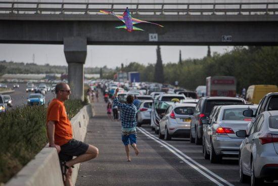 Un jeune Israélien fait voler un cerf-volant pour passer le temps alors qu'il est coincé dans un embouteillage sur la Route 6, dans le nord d'Israël, pendant les vacances de Pessa'h. Photo de Hadas Parush / Flash90