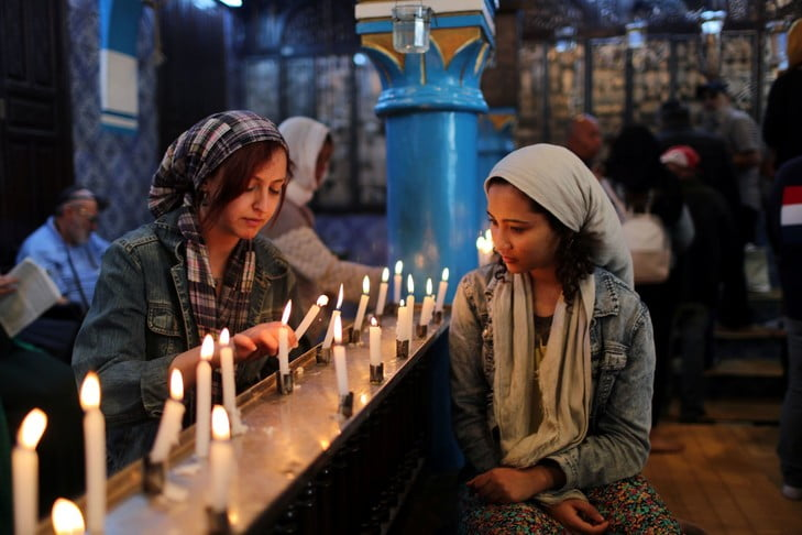 Cyrine Ben Said (L) and Amnia Ben Khalif, Muslim Tunisians, light candles during a religious ceremony at Ghriba, the oldest Jewish synagogue in Africa, during an annual pilgrimage in Djerba, Tunisia May 2, 2018. Picture taken May 2, 2018. REUTERS/Ahmed Jadallah - RC147A8FE240
