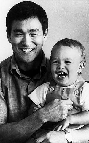 Bruce Lee avec son fils Brandon, blond aux yeux gris, vers 1966. (Crédit : domaine public)