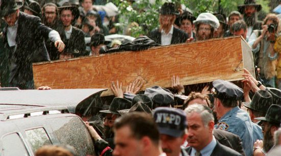 Des mains se tendent pour toucher le cercueil du Rabbi Menachem Schneerson alors que son cortège funèbre se prépare à quitter le siège mondial des Hassidim de Lubavitch, dans le quartier Crown Heights de Brooklyn, le 12 juin 1994 (Mark Phillips / AFP / Getty Images)