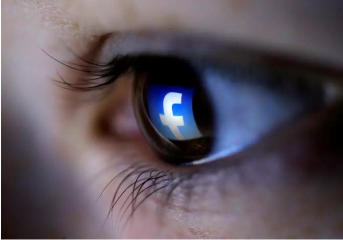 Une illustration montre un logo Facebook reflété dans les yeux d'une personne. (