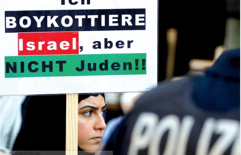 Un manifestant tient une pancarte indiquant «Je boycotte Israël, mais pas les Juifs» lors d'une manifestation marquant la fête d'Al Qods (fête de Jérusalem), à Berlin, le 1er juin