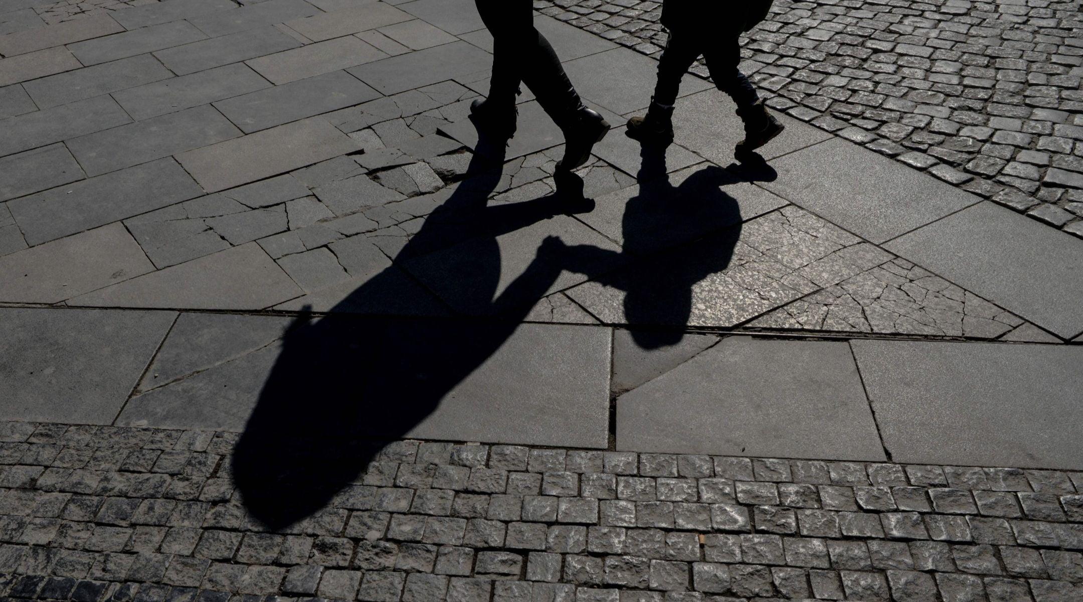 Les gens marchent sur le trottoir, dont certaines parties ont été fabriquées à partir de pierres tombales prises dans un cimetière juif, dans la zone piétonne de la place Wenceslas à Prague, le 20 mars 2018. (Michal CIZEK / AFP via Getty Images)