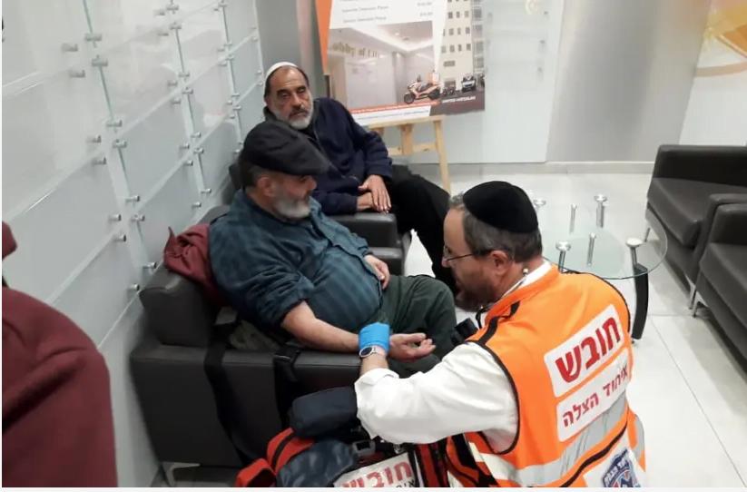 David Ben Avraham est traité par un ambulancier après sa libération de prison, tandis que l'ami Haim Pereg est assis à côté.