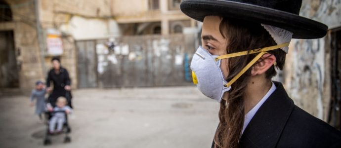 An ultra-Orthodox youth plays with a face mask in the Ultra orthodox jewish neighborhood of Mea Sharim, Jerusalem, on March 16, 2020. Photo by Yonatan Sindel/Flash90 *** Local Caption *** ??? ???? ?????? ????? ???????