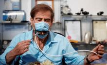 Meir Gitelis, co-développeur d'une société israélienne, mange tout en portant un masque muni d'une bouche mécanique qui s'ouvre pour permettre aux convives de manger sans l'enlever, comme les restrictions de la maladie du coronavirus (COVID-19) se relâchent, chez Avtipus Brevets et Inventions laboratoire à Or Yehuda, Israël 18 mai 2020 (crédit photo: AMIR COHEN / REUTERS)