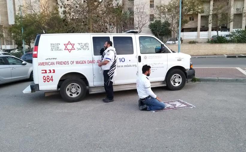 Deux ambulanciers paramédicaux, un juif portant un châle de prière et un musulman utilisant un tapis de prière, prient l'un à côté de l'autre près d'une ambulance Magen David Adom (MDA) à Beersheba, dans le sud d'Israël, le 24 mars 2020 (crédit photo: MOHAMD ALNBARE / MDA SPOKESPERSON)