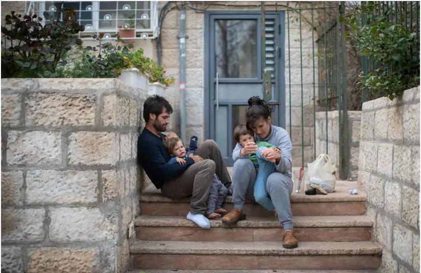 Une famille israélienne est assise sur les marches à l'extérieur de son immeuble à Jérusalem, alors qu'elle reste à la maison avec ses enfants pendant une quarantaine nationale, le 31 mars 2020. (crédit photo: HADAS PARUSH / FLASH90)
