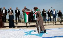 Une Palestinienne marche sur une réplique d'un drapeau israélien lors d'un événement marquant le Jour de la Terre près de la frontière entre Israël et Gaza alors que les rassemblements de masse prévus pour commémorer l'événement ont été annulés en raison de préoccupations concernant la propagation du coronavirus, à l'est de la ville de Gaza le 30 mars 2020 (crédit photo: REUTERS / MOHAMMED SALEM) Publicité