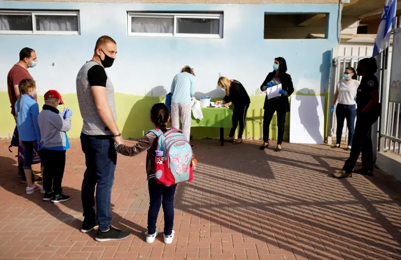 PHOTO DE DOSSIER: Les parents attendent avec leurs enfants pour entrer dans leur école primaire de Sderot qui rouvrira à la suite de la facilité des restrictions empêchant la propagation de la maladie à coronavirus (COVID-19) en Israël 3 mai 2020 (crédit photo: REUTERS / AMIR COHEN / FILE PHOTO)