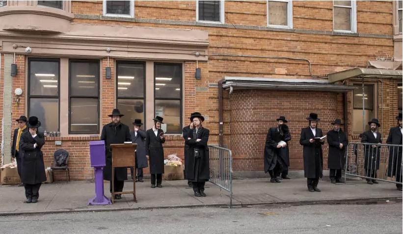Des hommes hassidiques prient à l'extérieur lors d'un service socialement éloigné dans le quartier de Borough Park à Brooklyn, le 30 mars 2020. (crédit photo: AVI KAYE)
