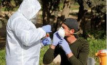 Un membre du personnel médical échange un travailleur palestinien contre un test de la maladie à coronavirus (COVID-19), à son retour d'Israël, à l'extérieur du point de contrôle de Tarqumiya sous contrôle israélien, près d'Hébron, en Cisjordanie occupée par Israël le 26 mars 2020 (crédit photo: MUSSA QAWASMA / REUTERS)