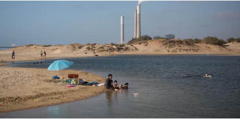 Une centrale électrique vue à l'arrière-plan de l'endroit où les Israéliens aiment nager dans un lac au bord de la plage de Zikim, dans le sud d'Israël, près de la frontière avec Gaza le 06 juillet 2015. (crédit photo: MIRIAM ALSTER / FLASH90)