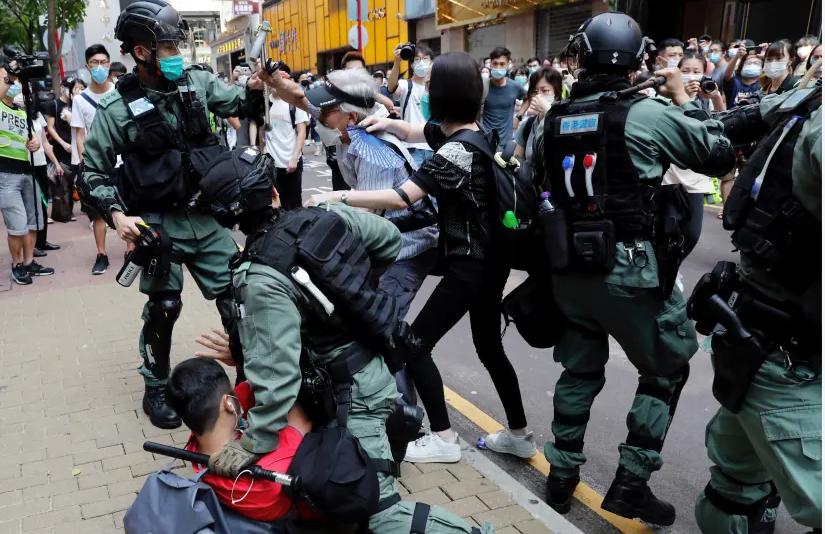 Des manifestants anti-gouvernementaux se disputent avec la police anti-émeute lors d'une manifestation à l'heure du déjeuner alors qu'une deuxième lecture d'une loi controversée sur l'hymne national a lieu à Hong Kong, Chine, le 27