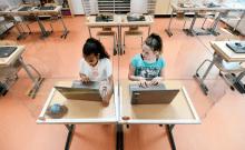 Les élèves assis derrière des cloisons en plexiglas assistent à une classe dans une école primaire (crédit photo: REUTERS)