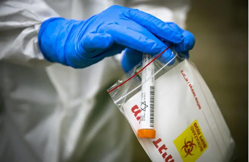 Des membres de l'équipe médicale du Magen David Adom, portant un équipement de protection, effectuent un test de coronavirus sur des patients à Jérusalem, le 17 avril 2020. (crédit photo: OLIVIER FITOUSSI / FLASH90)