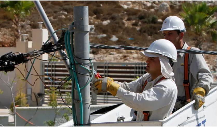 Des électriciens installent de nouvelles lignes de transport d'électricité sur un chantier de construction dans la ville cisjordanienne de Ramallah, le 3 septembre 2012. Crédit: REUTERS
