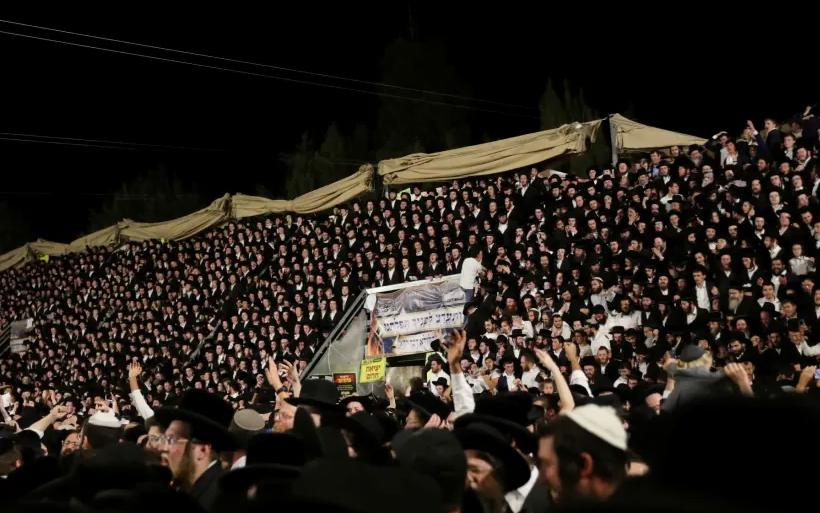 Les fidèles juifs chantent et dansent debout sur les tribunes lors de l'événement Lag B'Omer à Mount Meron le 29 avril 2021 (crédit photo: REUTERS / STRINGER)